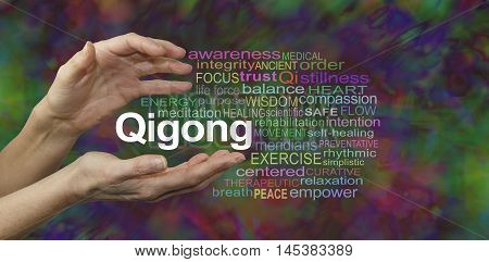 Qigong Healing word cloud - female cupped hands with the word QIGONG between surrounded by a word cloud on a rich dark multicolored background