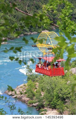 NIAGARA FALLS, CANADA. JUNE 28, 2016. Here we see many tourists suspended over the Mighty Niagara River sightseeing and enjoying the ride across the gorge on the Spanish Aerial Car.