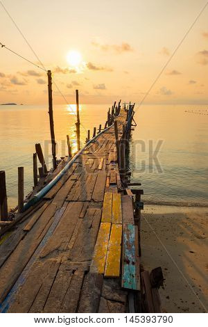 Jetty bridge made from wood during sunrise in dawn at Ao Lung Dam beach in Samet island Thailand.
