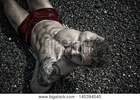 Handsome muscular shirtless man on the beach lying on gravel, looking at camera