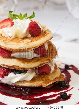 Crumpets with raspberry sauce whipped curd cheese and roasted almonds