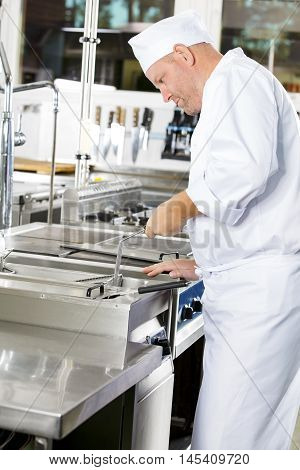 Close-up of a dedicated chef frying food in fryer at a professional kitchen. Industrial kitchen in restaurant or hotel.