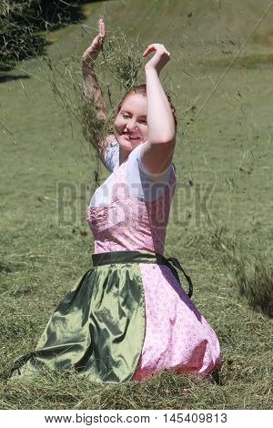Young farmer in dirndl kneeling in fresh hay in a meadow and forbidding flying hay with arms from.