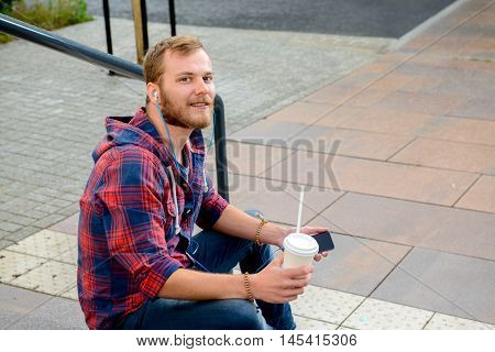 Young Man With Soft Drink Sitting On Stairs And Using His Phone