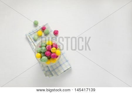 Bonbons in a glass over white wooden background, top view