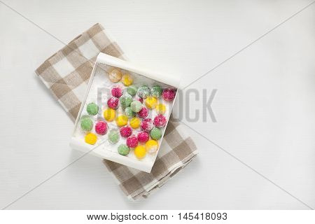 Bonbons in a box with powdered sugar, top view