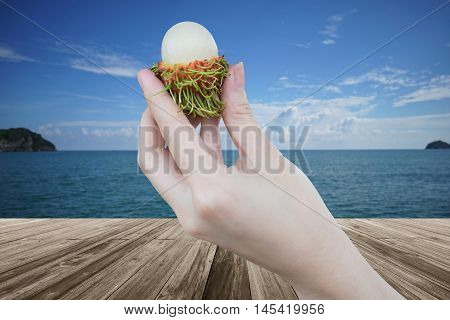 fresh Rambutan fruit in woman hand holding peeled rambutan with a perspective wooden table over blurred sea and blue sky in background