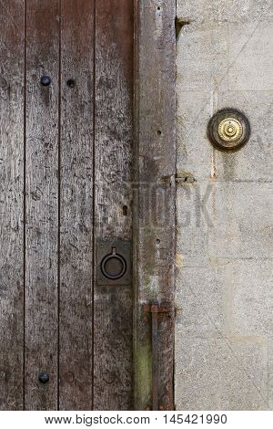 Old Rusty Metal Ring Handle On A Aged Timber Door With Brass Door Bell Button