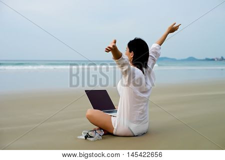 Girl With Arms Wide Open With Laptop At Beach