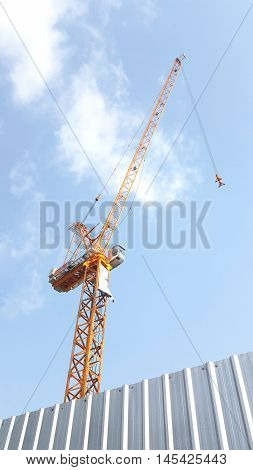 Crane against the blue sky. Yellow crane at the construction