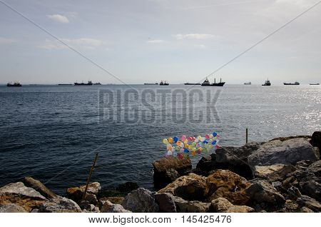 large cargo ships floating on the sea in the sunshine in front of the sea rocks with colorful balloons