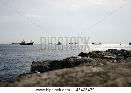large cargo ships floating on the sea in the sunshine in front of the sea stones
