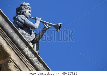 An old statue of a musician on top of the Clarendon Building in the historic city of Oxford England. The building is situated next to the Sheldonian Theatre.
