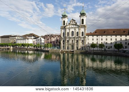 LUCERNE SWITZERLAND - MAY 09 2016: View towards the Jesuit Church located by the Reuss river in old town. It is widely believed to be the most beautiful Baroque church in Switzerland
