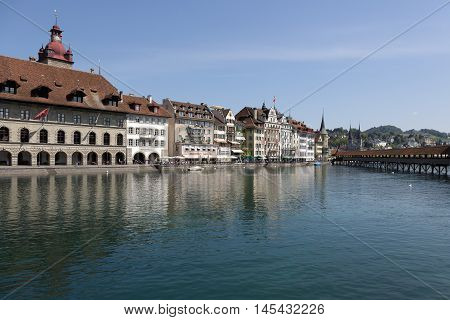 LUCERNE SWITZERLAND - MAY 05 2016: Townhouses down by the river Reuss shows the unique character of the city and variety of sightseeing attractions. The town is a destination for many travelers