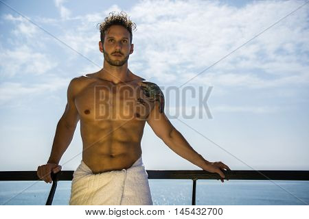 Muscular young man leaning on metal hand-railing on cruise ship, looking at camera