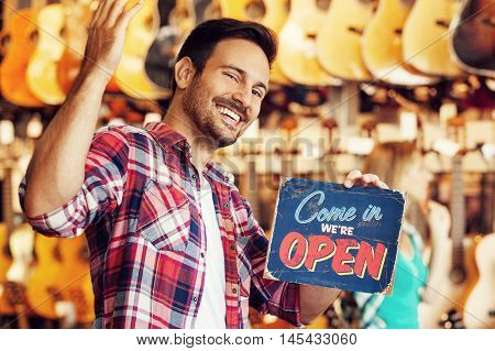 Musical intruments store. Young sale person is showing open store sign.