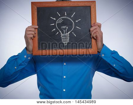 Businessman holding a chalkboard with a hand drawn lightbulb Great idea concept