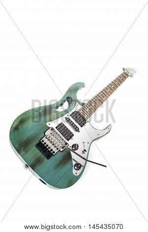 A used and slightly road-worn modern electric guitar. Studio shot against white background.