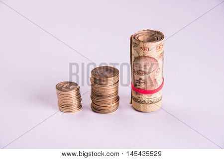 Roll of Indian Currency Rupees Notes and Coins and earthern piggy bank or money box