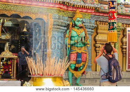 SINGAPORE, REPUBLIC OF SINGAPORE - JANUARY 08, 2014: The tourist take photo of Hanuman's statue. Sri Krishnan Temple, Singapore