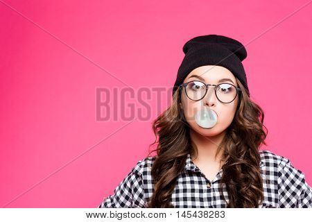 Fashion Model girl isolated over pink background. Beauty stylish woman posing in fashionable clothes and glasses. High fashion urban style. inflate the balloon of bubble gum.