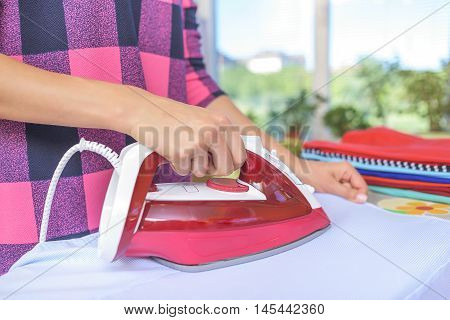 The woman to iron the clothes on an ironing board.