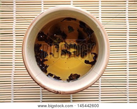 Making tea in a glass teapot on woven bamboo background