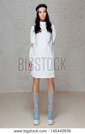 Woman in white dress- straitjacket, keeps herself in her hands, looking into the camera, socks with shoes on platfoma head bandaged. Sad model in blue tankette staying in studio with brick walls