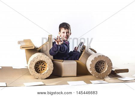 photo of young racer on a cardboar racing car on blue background. Boy showing ok gesture.