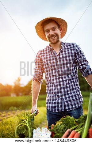 Likable farmer with smile on work in garden