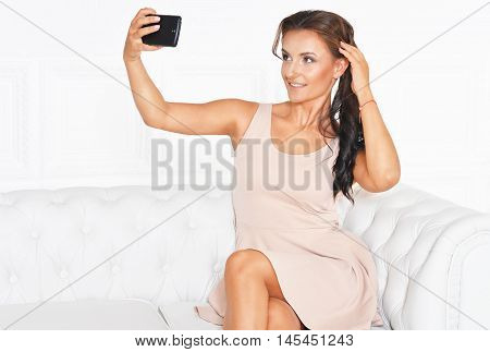 Young beautiful brunette posing in a beige dress making selfie  on white sofa