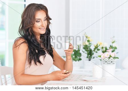 Young beautiful brunette  holds the phone and drinking coffee in the kitchen