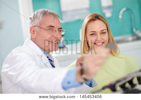 Male dentist shows dental film to female patient