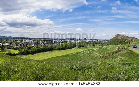 Panoramic summer view across Holyrood Park with Salisbury Crags looming over Edinburgh Scotland with the Castle on the horizon