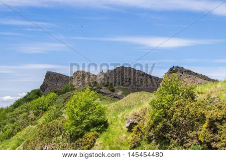 Man on top of the rugged volcanic rock formations of Salisbury Crags in Edinburgh gives a sense of scale