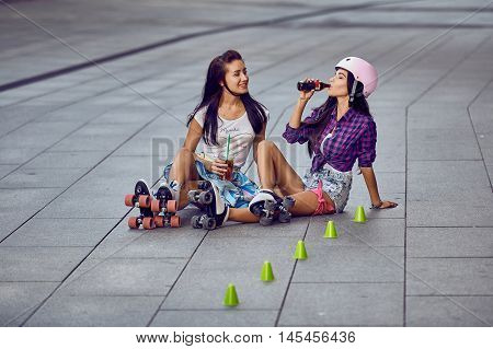 Beautiful hipster girls in roller skates resting and drinking lemonade. Beautiful and fashion young women posing having fun in urban skate park.
