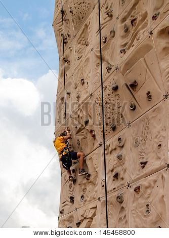 young girl climbing wall at outdoor fair
