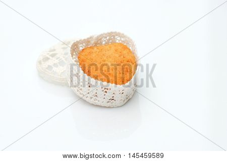 Cake in a casket in the form of heart on a white background