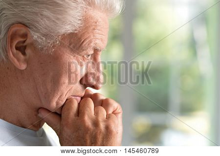 sad handsome elderly man in the room