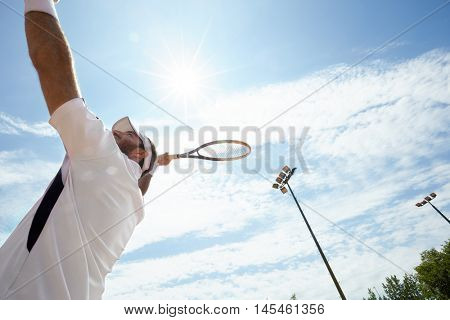 Tennis player serving ball on tennis court on shinny day