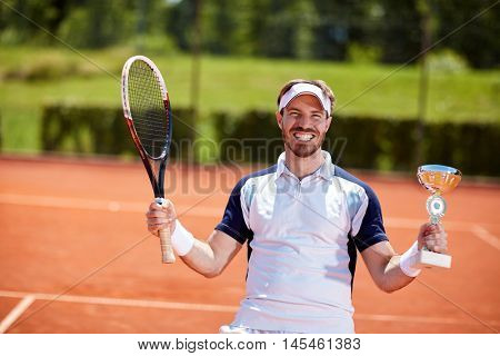 Male winner in tennis match with winner cup and racket