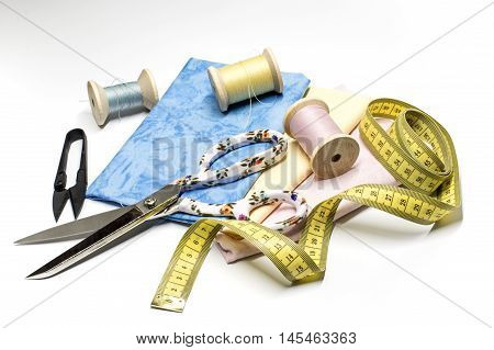 Sewing threads, scissors, fabrics and measuring tape