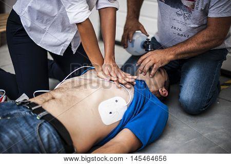 operators assisting an unconscious man with cardiopulmonary resuscitation