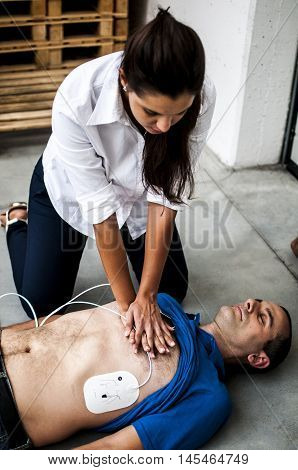 girl assisting an unconscious man with cardiopulmonary resuscitation