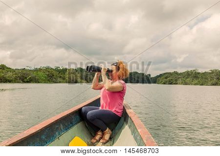 Happy Blonde Woman With High Power Binocular In Amazonian Jungle National Park Cuyabeno South America