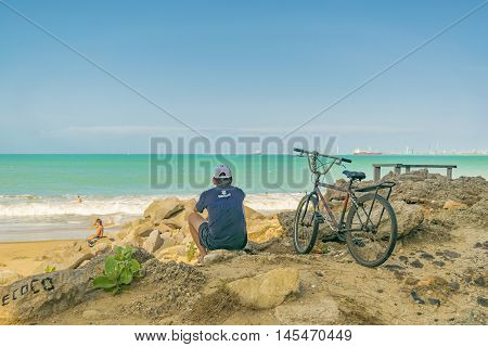 FORTALEZA, BRAZIL, DECEMBER - 2015 - Back view of adult man sitting on rock watching the beach in Fortaleza Brazil