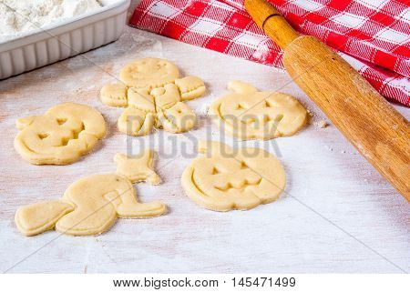 Making cookies for Halloween and Thanksgiving. Fun food for kids, a snack for a party. On a white wooden table carved shortbread dough, rolling pin, flour, towel