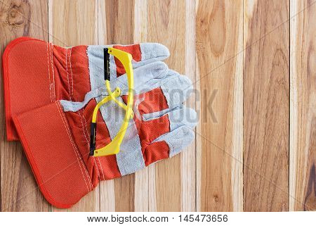 Protective gloves and goggles. Standard construction safety equipment on wooden table with copy space