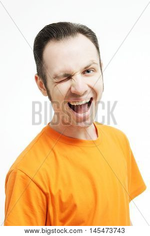 Close-up portrait of guy winking open-mouthed. Over white background. Winking guy with opened mouth . Crazy guy in an orange T-shirt.